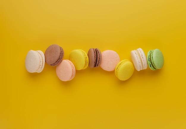 Makrone. bunter kuchen macaron mit pastelltönen, die auf gelbem hintergrund verstreut sind. draufsicht auf mandelkekse.