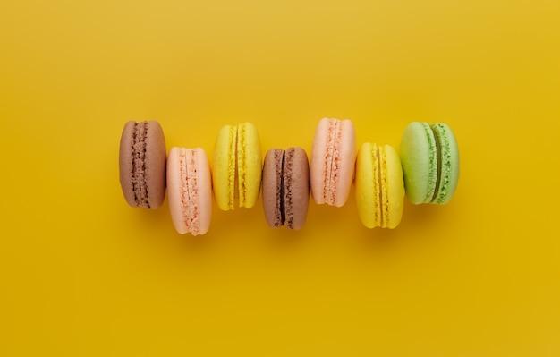 Makrone. bunter kuchen macaron mit pastelltönen, die nicht gleichmäßig in einer reihe auf gelbem grund gestapelt sind. draufsicht auf mandelkekse.
