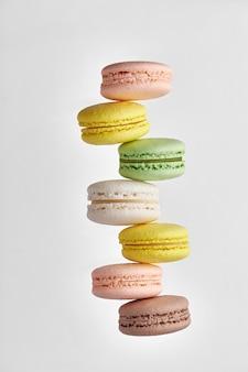Makrone. bunter kuchen macaron mit pastelltönen, die nicht gleichmäßig in einer reihe auf weißer wand gestapelt sind. draufsicht auf mandelkekse.