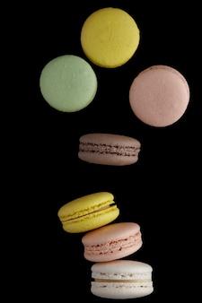 Makrone. bunter kuchen macaron mit pastelltönen fallen auf die stapelmakrone auf schwarzer oberfläche. draufsicht auf mandelkekse.