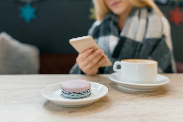 Makrone im teller, tasse kaffee, schönes blondes mädchen in der wolldecke mit smartphone