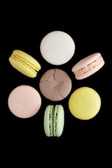 Makrone. sechs bunte kuchen macaron mit pastelltönen und einer rissigen liegen und stehen in form einer blume auf schwarzer oberfläche. draufsicht auf mandelkekse.