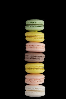 Makrone. stapel von buntem kuchen macaron mit pastelltönen auf schwarzer oberfläche. draufsicht auf mandelkekse.