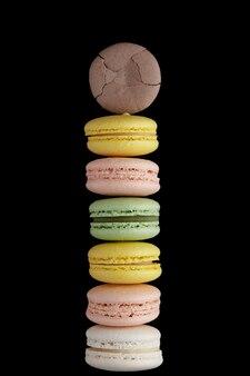 Makrone. stapel von sechs bunten kuchen macaron mit pastelltönen und einer auf schwarzer oberfläche geknackt. draufsicht auf mandelkekse.