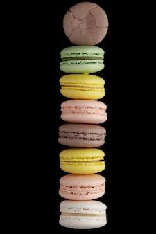 Makrone. stapel von sieben bunten kuchen macaron mit pastelltönen und einer auf schwarzer oberfläche geknackt. draufsicht auf mandelkekse.