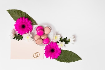 Makronen auf Platte zwischen Blumen, Blättern, Papier und Ringen
