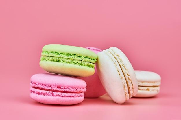 Makronen auf rosa hintergrund. bunter kleiner keks aus gemahlenen mandeln und kokosnuss