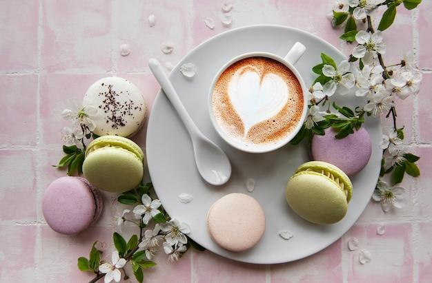 Makronen mit einer tasse kaffee und einem zweig weißer blumen auf einer rosa fliesenoberfläche tile