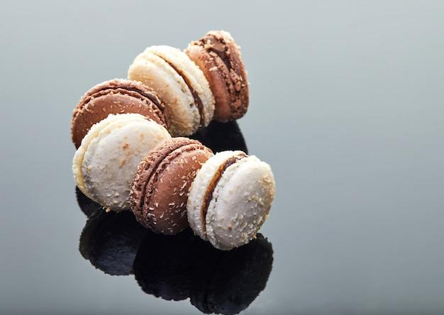 Makronen mit kokosgeschmack auf einem grauen hintergrund mit reflexion