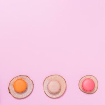 Makronen über dem baumstumpf gegen rosa hintergrund mit copyspace für das schreiben des textes