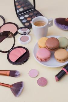Makronenfrühstück mit kaffee und kosmetikprodukt auf beige hintergrund