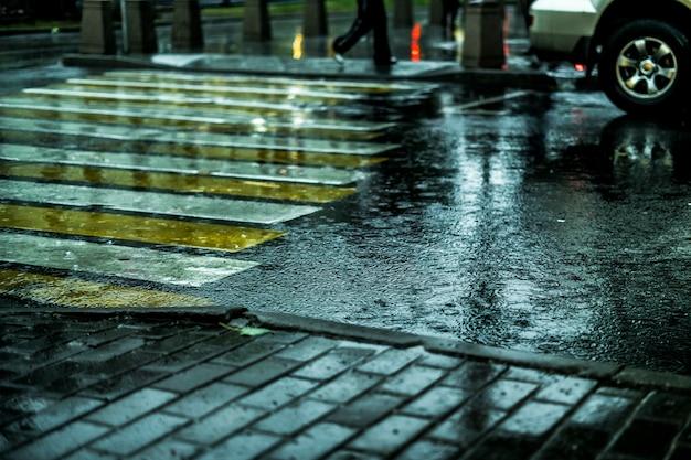 Makroschuß des nassen stadtstraßen-bodenkopfsteins während des regens in europa