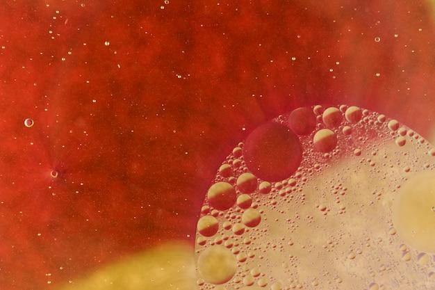 Makroschuß des öls fällt auf rot farbigen hintergrund