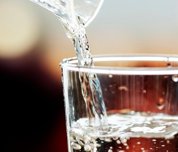 Makroschuß des strömenden wassers in ein glas