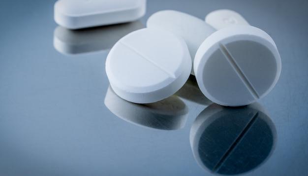 Makroschuß von weißen tablettenpillen auf silbernem hintergrund mit schatten.