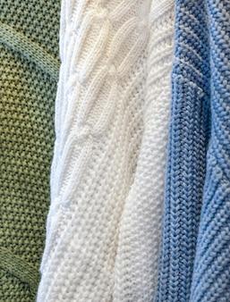 Makrotextur von drei pullovern. stofffaser grüner, weißer und blauer hintergrund.