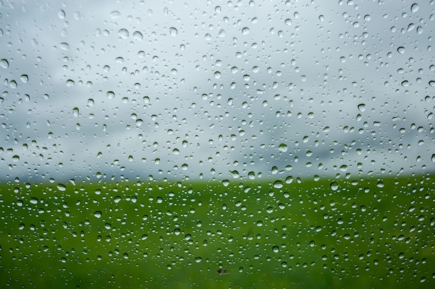 Makrotextur von regentropfen auf fensterglas im hintergrund ein bewölkter himmel nach regen und grünem feld