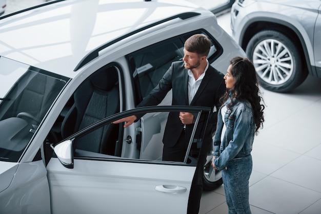 Mal sehen, was drin ist. weiblicher kunde und moderner stilvoller bärtiger geschäftsmann im automobilsalon.