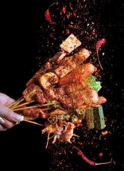 Mala gegrillter grill (bbq) mit sichuan-pfeffer, mit fallenden gewürzen mala-pulver und chili, scharf und würzig und leckeres street food.