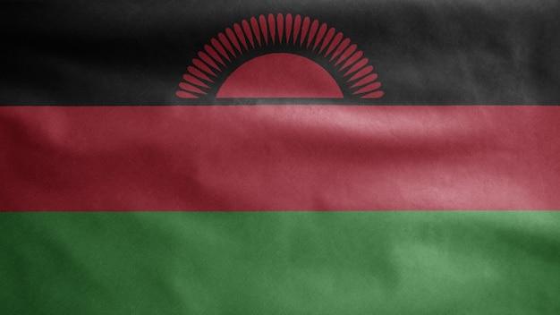 Malawische flagge weht im wind. malawi-banner weht, weiche und glatte seide. stoff textur fähnrich hintergrund.