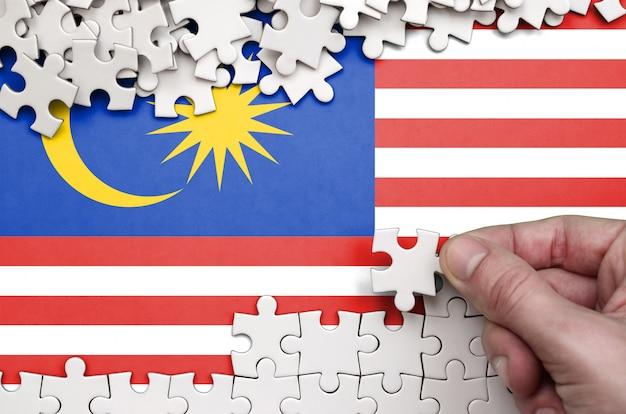 Malaysia flagge ist auf einem tisch dargestellt, auf dem die menschliche hand ein puzzle der weißen farbe faltet