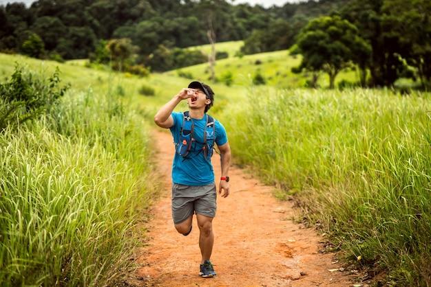 Male runner of trail er lief schnell auf dem berg. er trinkt