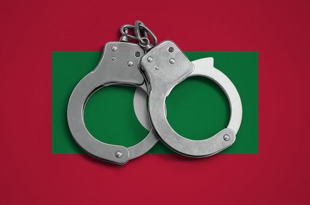 Malediven flagge und polizei handschellen. das konzept der einhaltung des gesetzes im land und des verbrechensschutzes