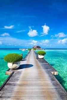 Malediven wasserbungalows resort am inselstrand. indischer ozean, malediven. schöne meereslandschaft, luxusresort und himmel. strand unter herrlichem himmel