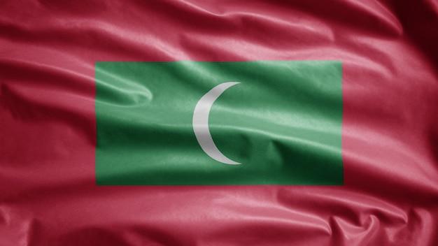 Maledivische flagge weht im wind. malediven-banner weht weiche seide. stoff textur fähnrich hintergrund