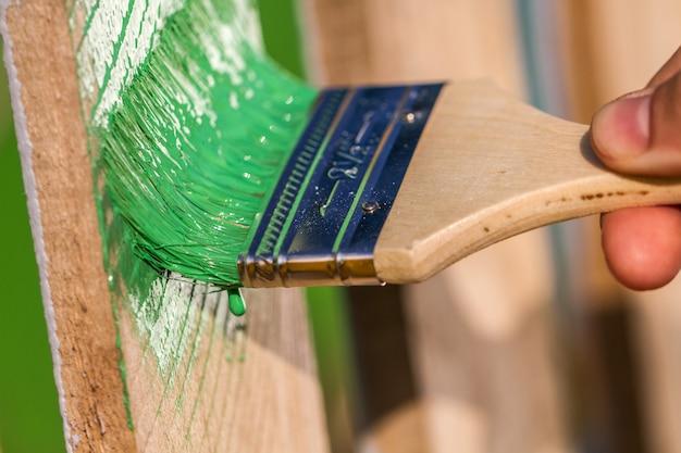 Malen eines bretterzauns mit grüner farbe. reparatur . holzbürste hautnah.