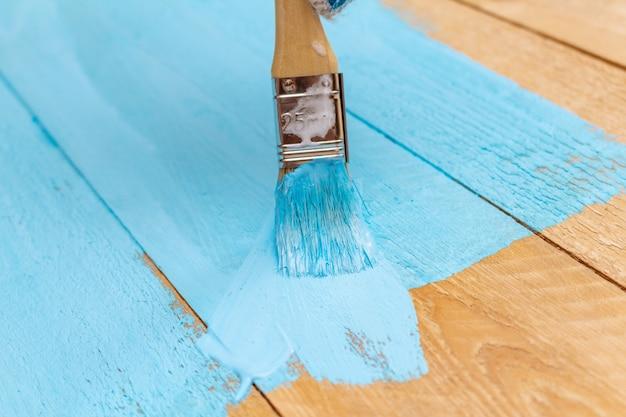Malen mit dem pinsel blaue farbe auf dem holztisch
