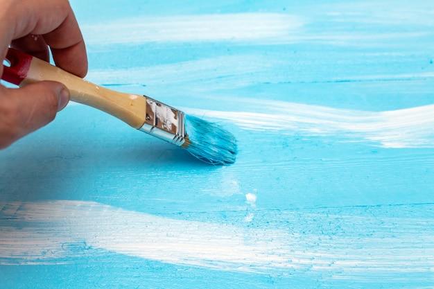 Malen mit dem pinsel blaue farbe farbe auf der grünen farbwanne auf dem holz diy