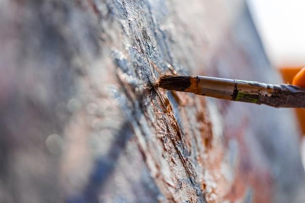 Malen mit einem alten pinsel auf der leinwand