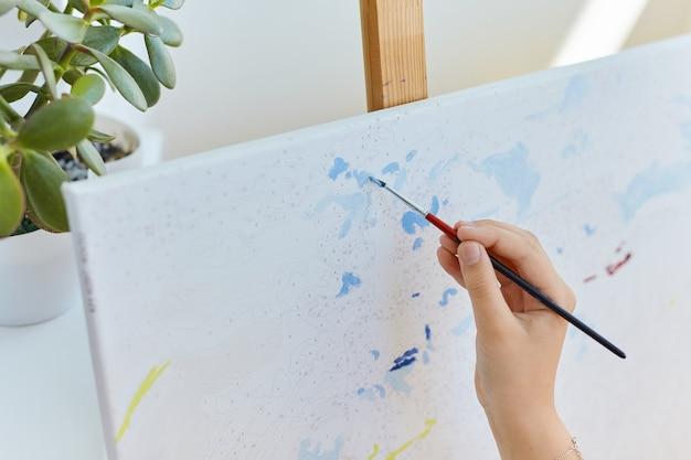 Malen nach zahlen hautnah. kinderhandzeichnung mit pinsel auf nummerierter leinwand. kreatives hobby und freizeit. malerei für anfänger. kunst idee. hell und bunt.