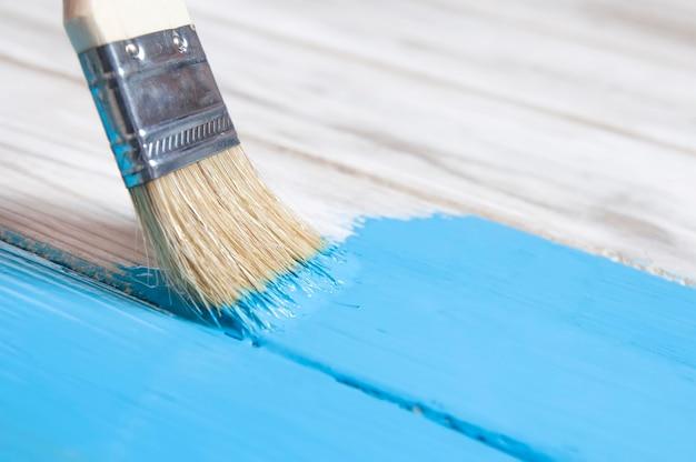 Malen sie mit einem pinsel blaue farbe weiße alte bretter seitenansicht