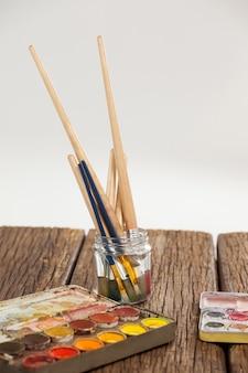 Malen sie pinsel in einem glas mit wasser und aquarellen auf holztisch gefüllt