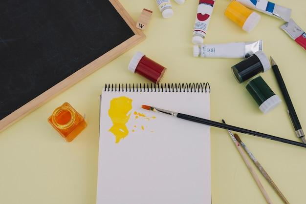 Malen und tafel in der nähe von skizzenbuch