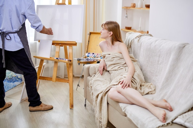 Maler an der staffelei zeichnet weibliches modell, das auf sofa, im hellen studioraum sitzt. kunstkonzept