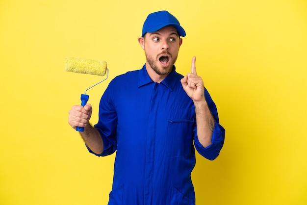 Maler brasilianischer mann isoliert auf gelbem hintergrund, der eine idee denkt und mit dem finger nach oben zeigt