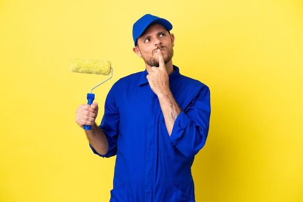 Maler brasilianischer mann isoliert auf gelbem hintergrund, der zweifel hat, während er nach oben schaut