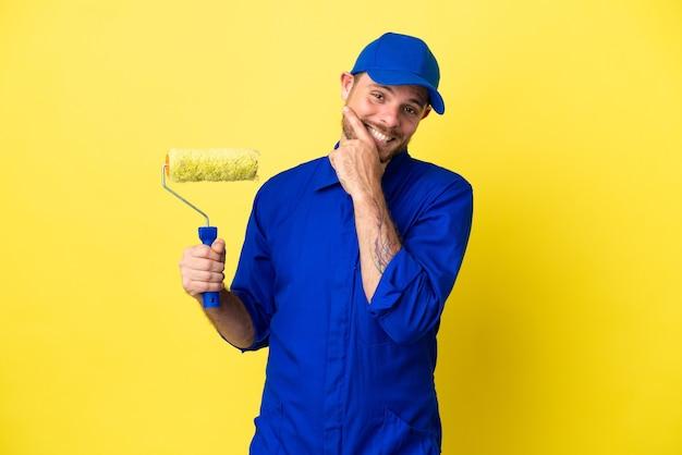 Maler brasilianischer mann isoliert auf gelbem hintergrund glücklich und lächelnd