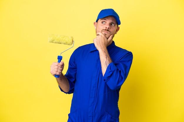 Maler brasilianischer mann isoliert auf gelbem hintergrund mit zweifeln having