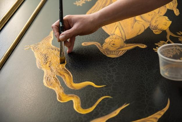 Maler-dekorateur zeichnet mit einem breiten, dünnen pinsel