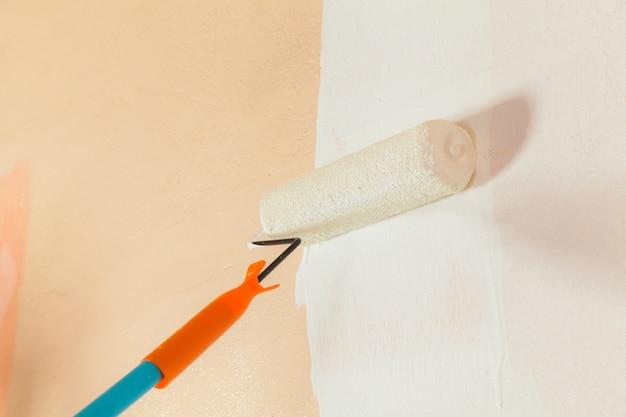 Maler, der die wände weiß im haus malt
