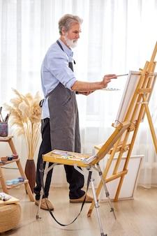 Maler, der meisterwerk schafft, älterer mann, der auf leinwand arbeitet, mit farben, pinseln, staffelei und anderen werkzeugen