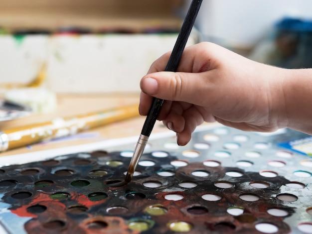 Maler, der seine farbpalette verwendet