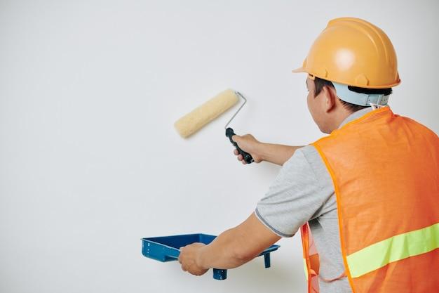Maler, der weiße farbe aufträgt