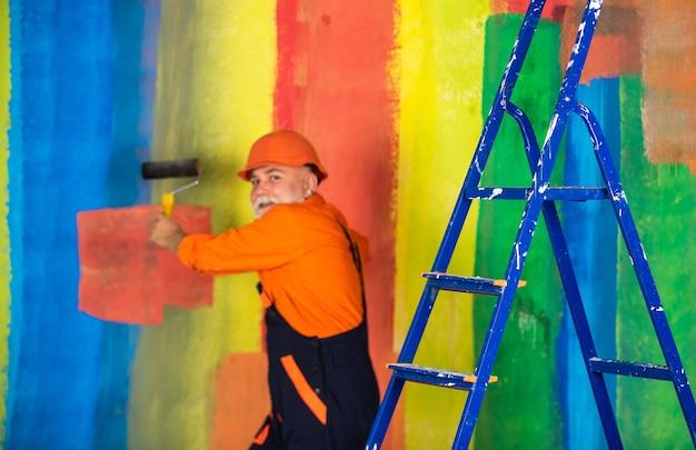 Maler des älteren mannes verwenden rolle auf leiter. die wand bunt streichen. professioneller maler in arbeitskleidung. arbeiter malerei wand im zimmer. männlicher dekorateur malerei mit rolle. alles reparieren.