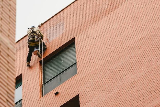 Maler hockte an den wänden eines gebäudes mit seilen hängen.
