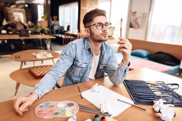 Maler holds paintbrush looking sitzt am schreibtisch